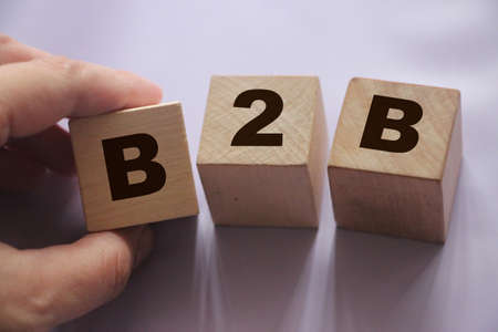 B2B abbreviation in letters on wooden cubes. Business or Busness concept Hand put a cube B to the row. Business marketing strategy concept.