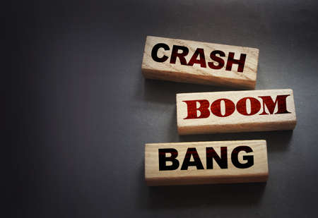 Crash boom bang words on wooden blocks on black. crisis concept