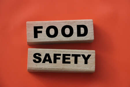 Wooden block with words FOOD SAFETY on tomato red. Healthcare concept