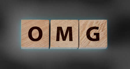 OMG written on a wooden cubes on black gradient background. Oh Mine God exclamation shocking concept