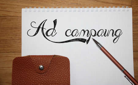 Ad Campaign words written on copybook page, brown leather wallet and pen on wooden table. Marketing advertising concept.