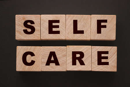 Self care words on wooden blocks with letters, self treatment healthcare concept, top view dark grey background