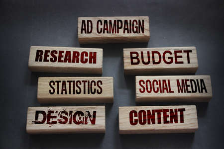 AD CAMPAIGN research budget statistics social media design conctent words on wooden blocks. Marketing advertising concept.