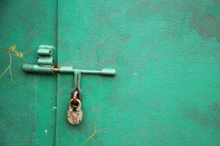 Old lock hangs on a bright green garage door. Locked data or secret information concept