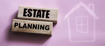 Estate planning on Wooden blocks on pink background. Real estate business concept.