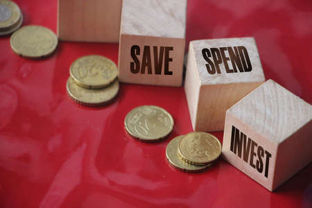 Save spend invest on Wooden Cubes and coins on red backgroud. Financial business personal account concept.