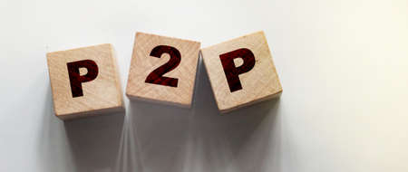 P2P abbreviation written in wooden blocks. Peer to peer business concept. Wooden abc.