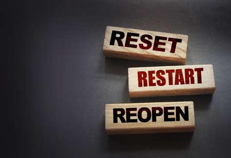 Reset, restart, reopen on wooden blocks on black background. Post pandemic world concept. Stock Photo