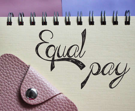 Handwriting text writing Equal Pay. Words on spiral copybook and pink leather wallet. Concept meaning eliminating and race discrimination in wage systems