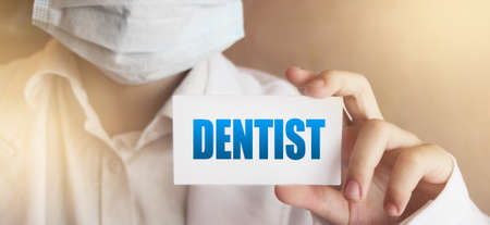 A doctor holds a card with word Dentist. Medical healthcare concept.
