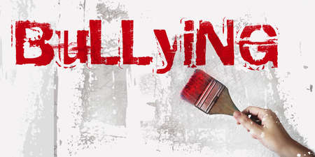 Bullying, written with red paintbrush on a wall. Conceptual image.