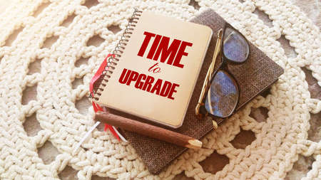 Time to upgrade text on the cover of notebook, glasses and pen on crochet cloth. Business renew concept. Stock fotó