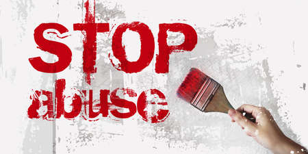 stop abuse hand with paintbrush on the grunge white wall.