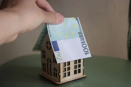 Hand puts 100 Euro bill like roof on symbolic small toy vineer house. Buying property, safety and mortgage real estate business concept