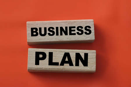Business plan words on wooden blocks on red. Marketing and management concept.