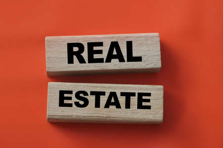 Real estate text on wooden blocks on red background. Business concept. Rent, buy property concept.