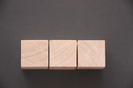 Wooden cube block shape withcopyspace on dark gray table.