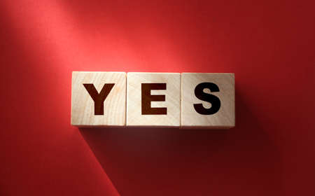 The word Yes written in black letters on wooden blocks. Message spells Yes on white background. Business, motivation and education concept