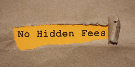The message No Hidden Fees appearing behind torn brown paper. Business accounting concept 免版税图像