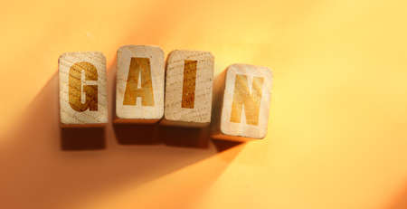 Gain word on wooden blocks on orange. Interest rate growth concept, business profit concept.