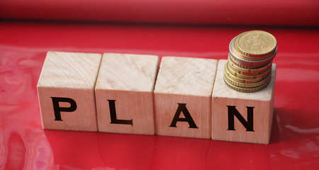 Wooden Blocks with the text: Plan and coins. Business plan. Imagens