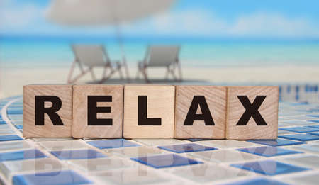 Relax - an inscription on wooden cube blocks on sunny beach beckground with reflection. Reduce stress mental health concept Banque d'images