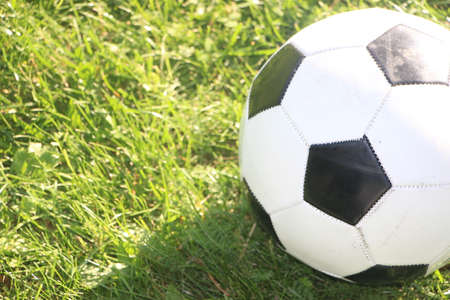 Classic soccer ball, typical black and white pattern, placed on the free kick spot of the stadium turf. Traditional football ball on the green grass field of arena.