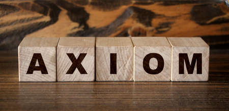 Axiom word made with building blocks. A row of wooden cubes with a word written in black font. Banque d'images