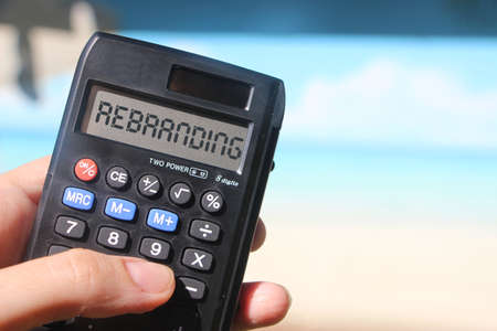Rebranding on display of Calculator in hand sitting on summer beach. Marketing business concept. Banque d'images
