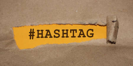 The word hashtag appearing behind torn paper.