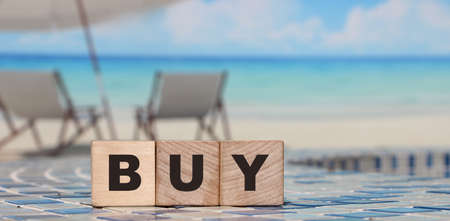 Shopping concept. Wooden cubes with word BUY on the wooden table.