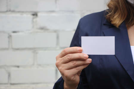 Businesswoman showing and handing a blank business card. Business woman in dark blue suit. Business concept