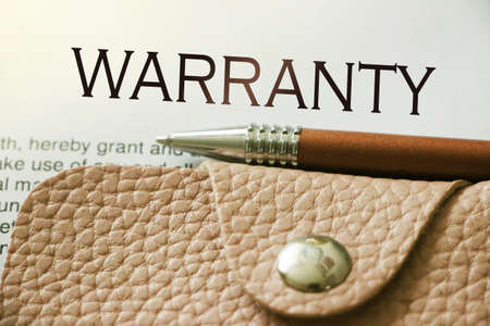 Warranty words on top of page, beige leather wallet, luxury pen. Business concept Stock Photo