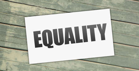 Equality word on card put on grunge wooden background. Teamwork equality and diversity Concept.