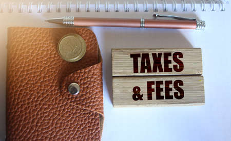 Taxes and fees Text on the wooden blocks, wallet and coins. Business concept.