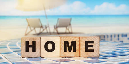 Wooden cubes with the word home, home on a wooden background. Emigration consept. Banque d'images