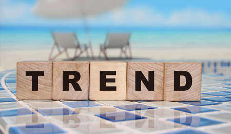 Trend word on cube blocks on relaxed ocean beach background. Business and fashion concept.