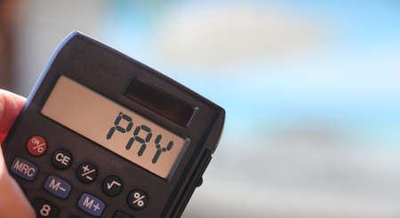 Pay word on calculator display. Business and tax concept.