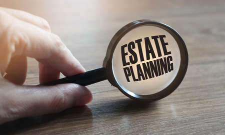 Estate planning words under, agnifying glass on wooden table. Real estate business concept.
