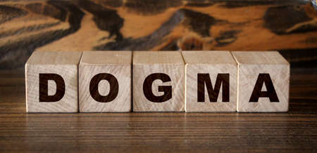 Dogma Word In Wooden Cubes. Social concept. Banque d'images