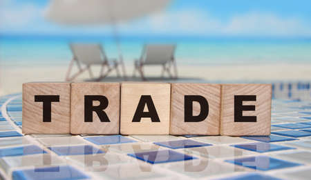 Trade word on Wooden cubes on red. Business deals Concept.