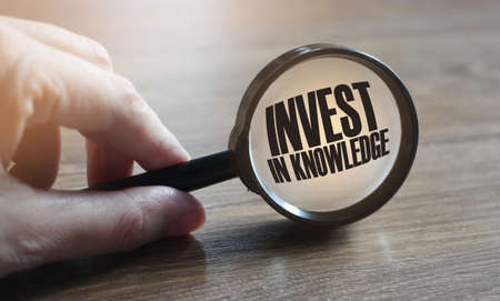 Invest in Knowledge text under magnifying glass in hand, on wooden table. Business education concept.