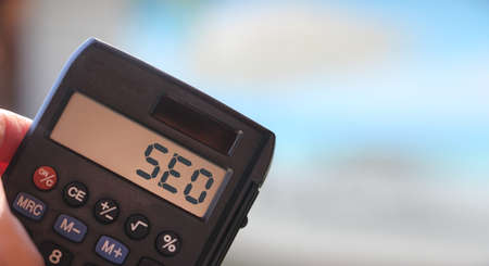 the word SEO, acronym for Search Engine Optimization, on the display of a calculator. Business technology concept. Banque d'images