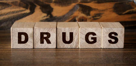 Drugs word on light wooden cubes on wooden table. Healthcare medical concept.