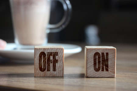 Two wooden blocks with inscription OFF and ON and cup of cacao. Selective focus. Business and healthcare concept.