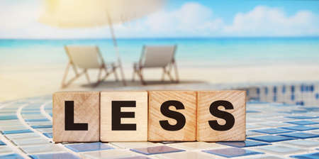 Less word on wooden alphabet blocks on relaxed beach ocean landscape background. Less spend, more saving business concept.