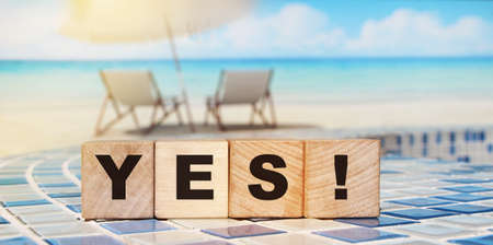 The word Yes written in black letters on wooden blocks in ocean landscape background. Business, motivation and education concept. Vacation and relax concept