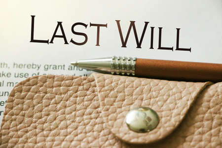 Last will words, pink leather wallet and pen. Legacy concept.