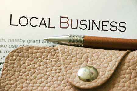 local business, text on page, beige leather wallet and luxury pen. Small business concept. Banco de Imagens