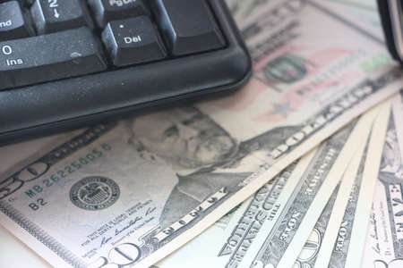 Close-up of money bills in dollars, under keyboard of the laptop. Remote earnings on the Internet.Home and office work in isolation, online business concept